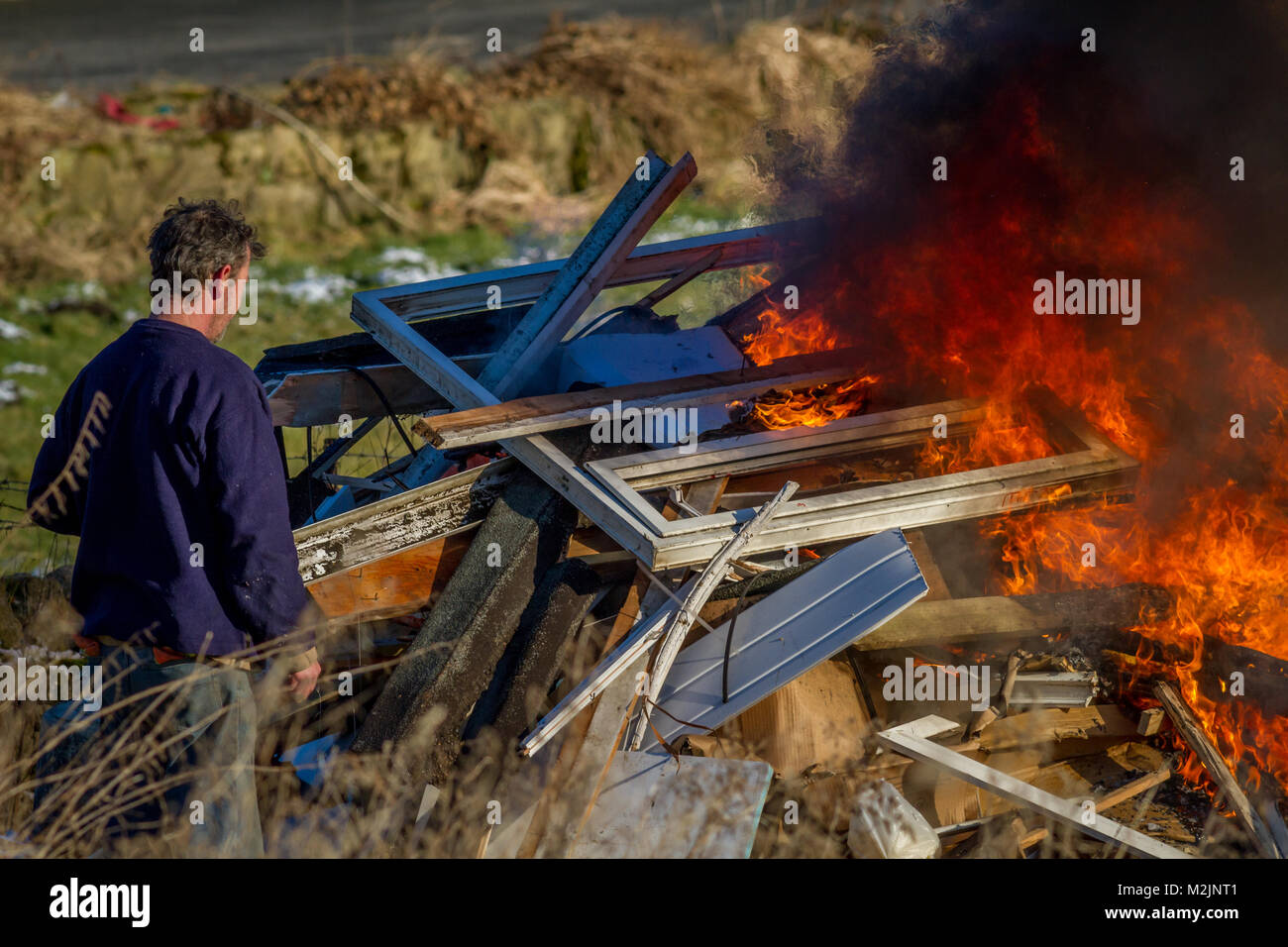Person monitoring a burning fire of rubbish from a house renovation with flames and black smoke, probably with toxic - Stock Image