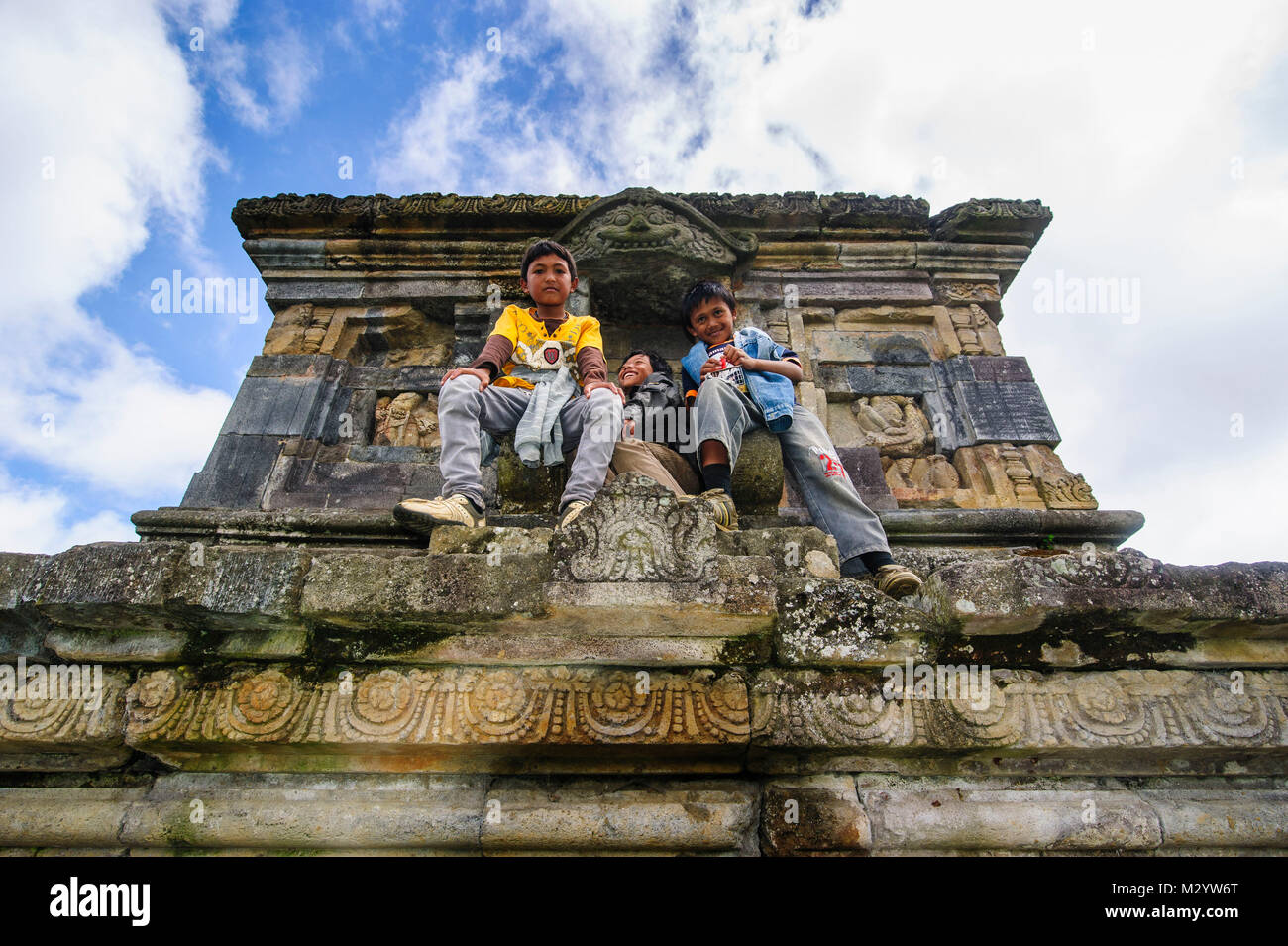 Young boys sitting in a temple of the Arjuna Hindu Dieng temple complex , Dieng Plateau, Java, Indonesia - Stock Image