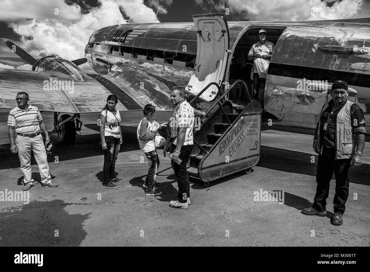Passengers board a Douglas DC-3 aircraft at the runway of the airport in Barranco Minas, Colombia. - Stock Image