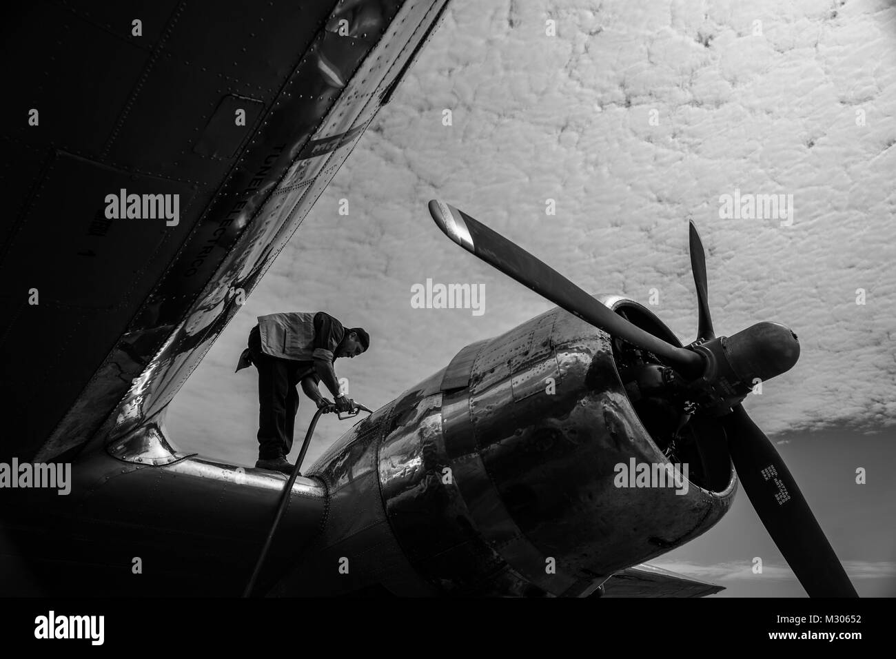 A Colombian mechanic refuels a Douglas DC-3 aircraft at the airport of Puerto Inírida, Colombia. - Stock Image