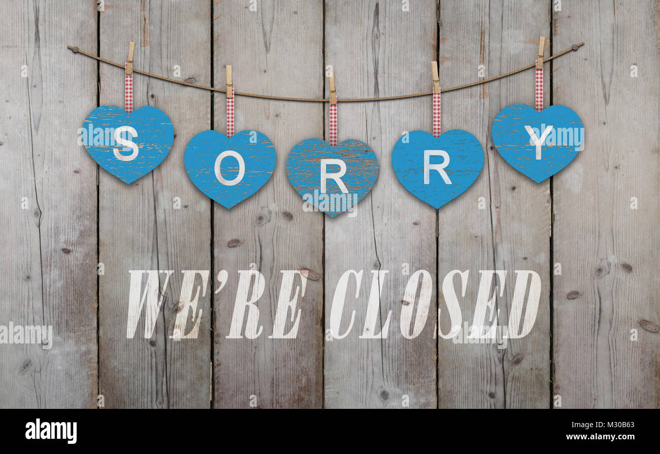 blue wooden hearts with text sorry we are closed, on old scaffolding wooden backdrop, with copy space - Stock Image