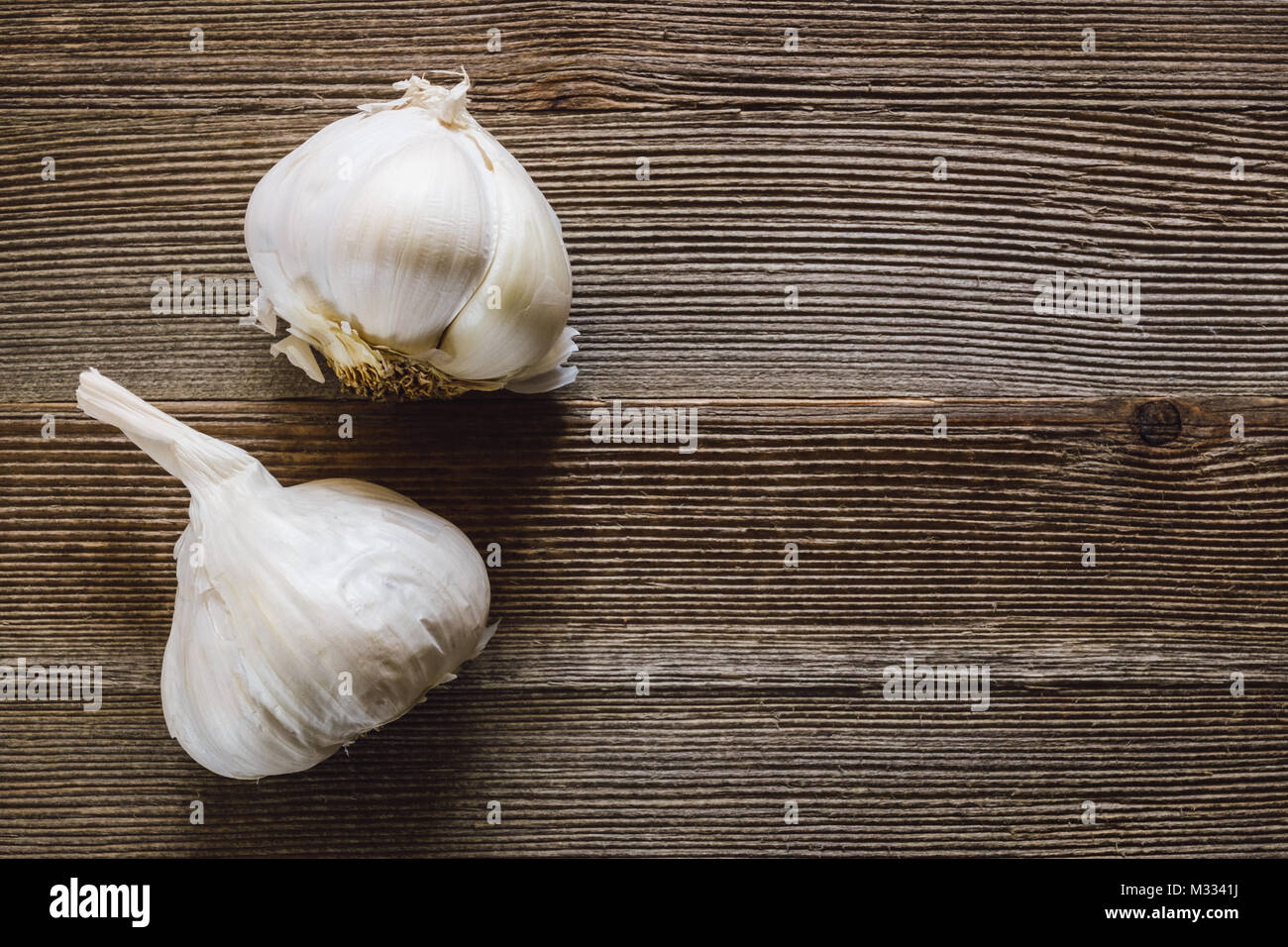 Heads of Garlic on Rustic Wooden Table with Room for Copy - Stock Image
