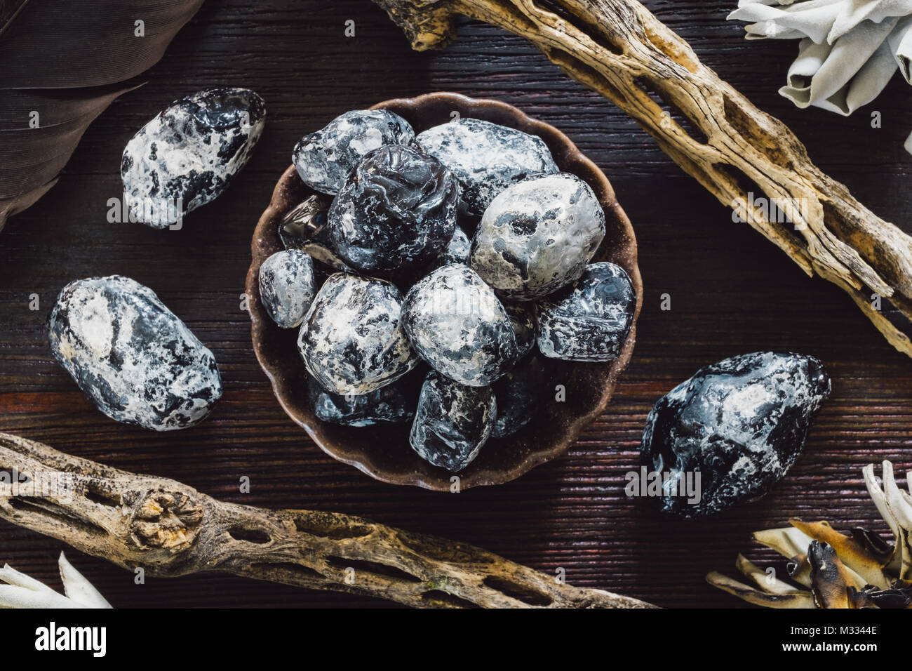 Apache Tear Obsidian on Dark Table with Cholla, Sage and Crow Feather - Stock Image