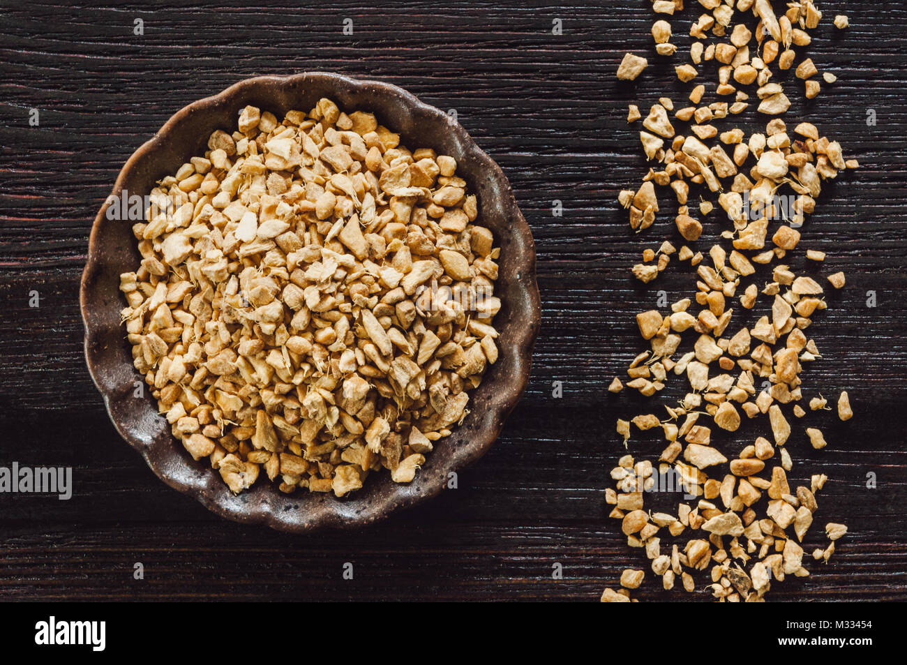Ceramic Bowl of Dried Ginger with Arranged Granules on Dark Wooden Table - Stock Image