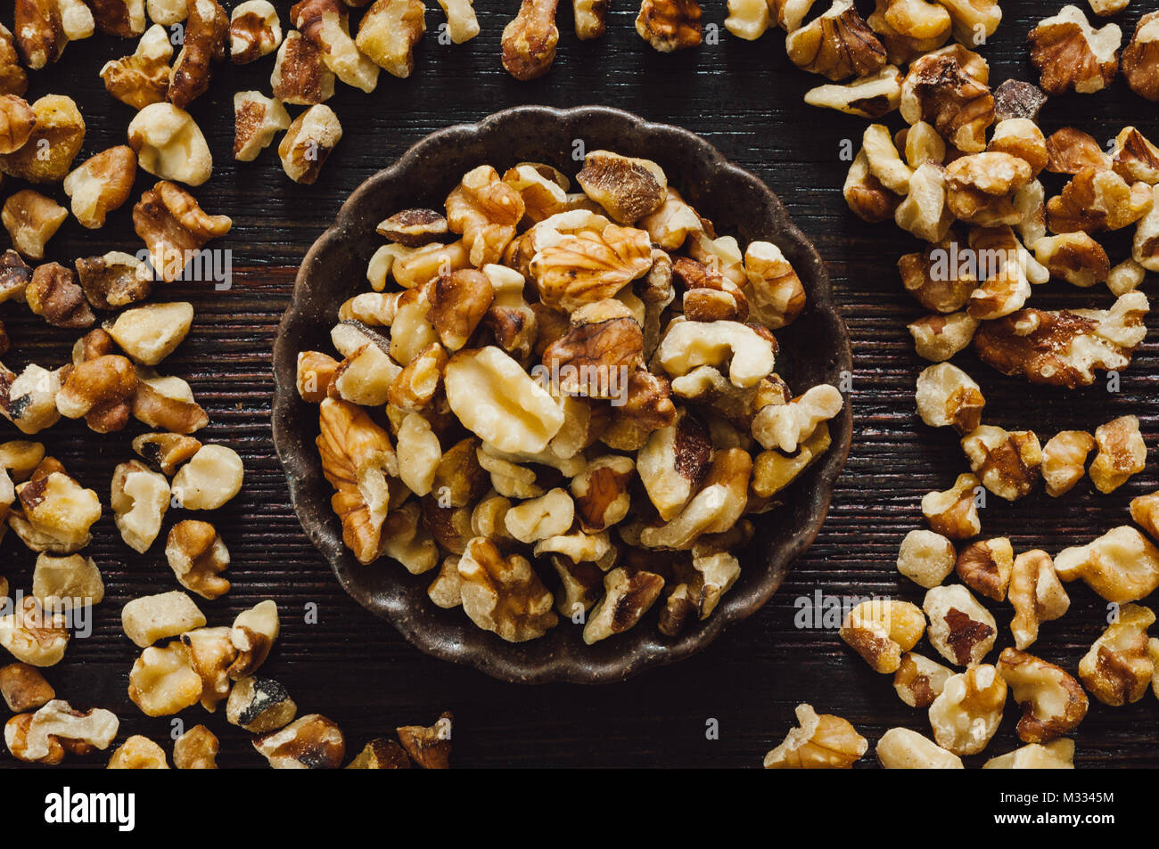 Chopped Walnuts Arranged on Dark Table - Stock Image