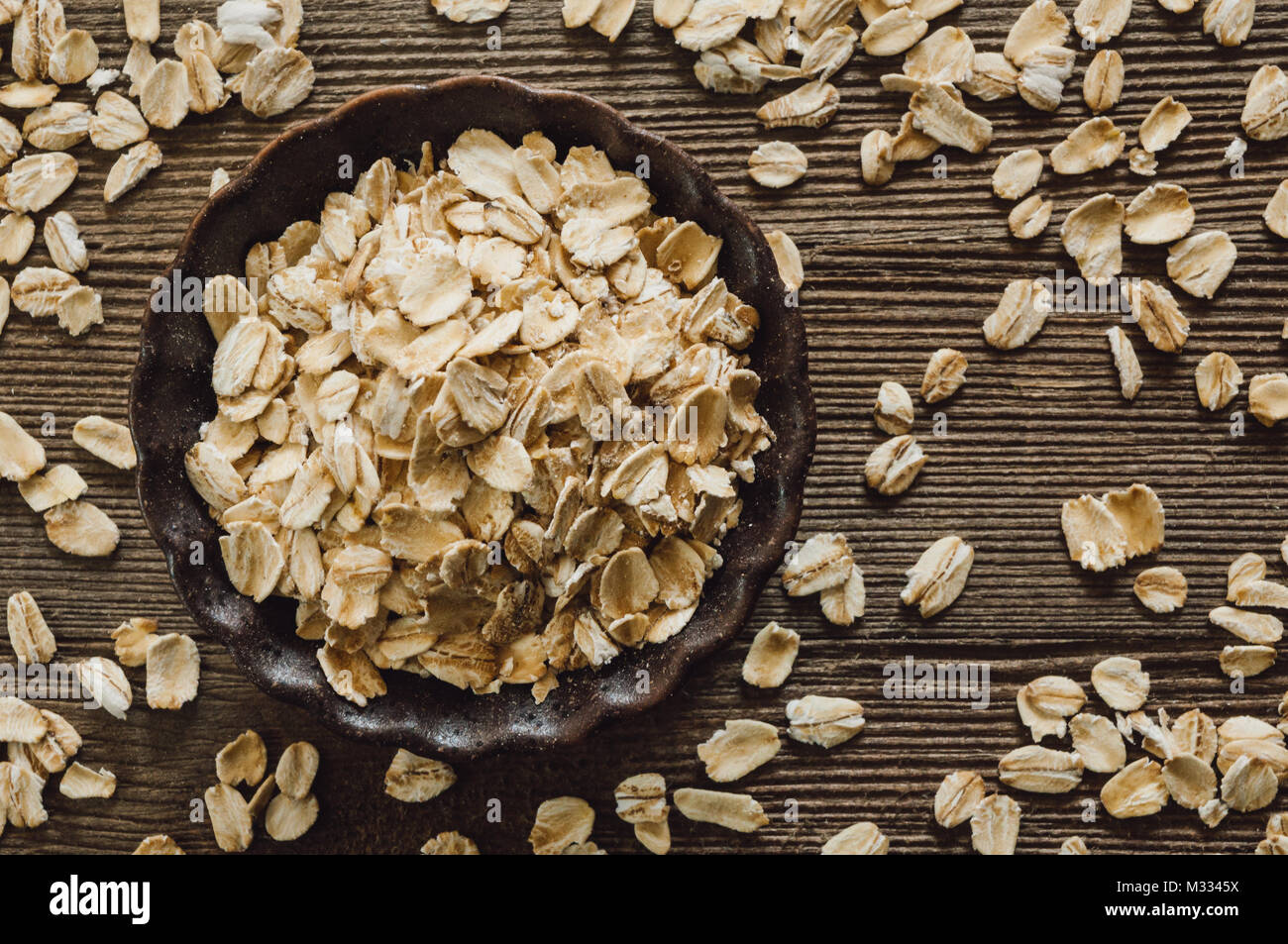 Ceramic Bowl of Rolled Oats on Rustic Wooden Table - Stock Image