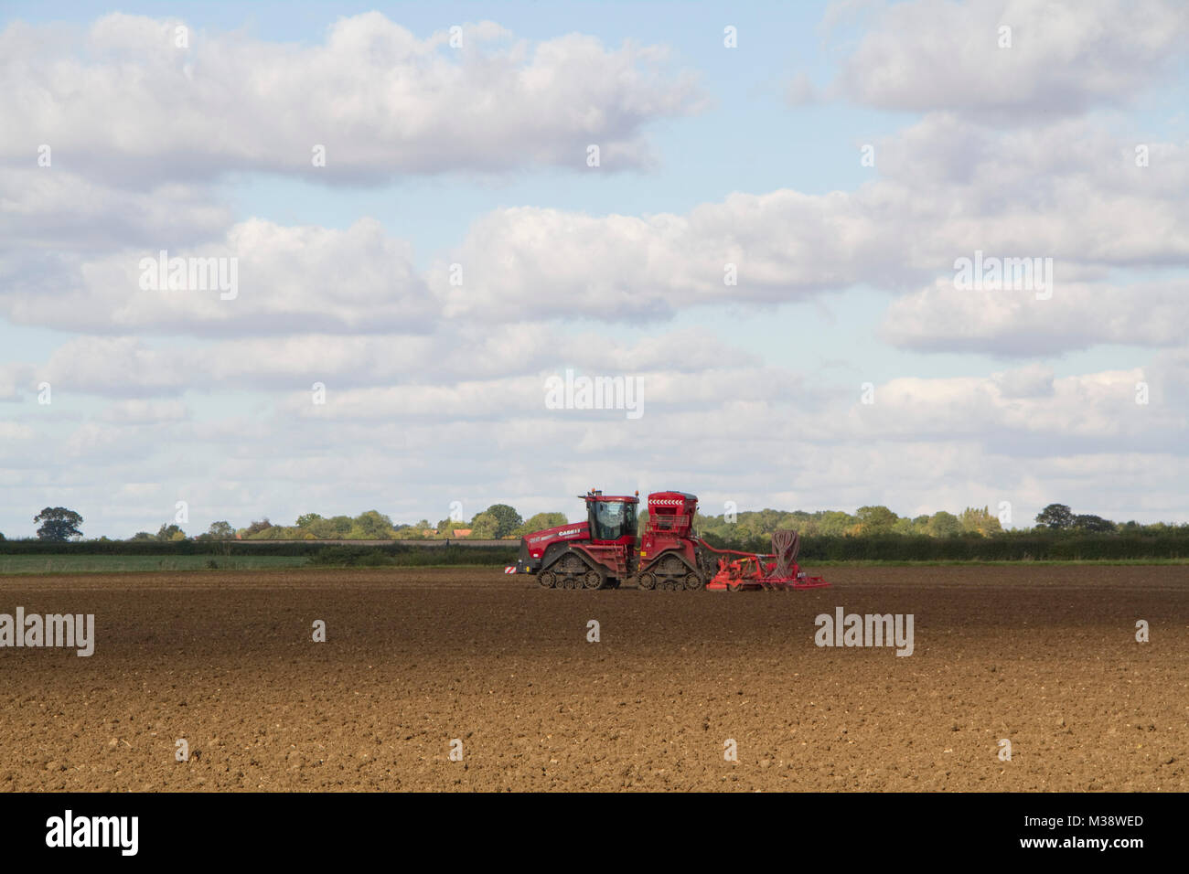 Red tracked farm vehicle doing something in a field - Stock Image