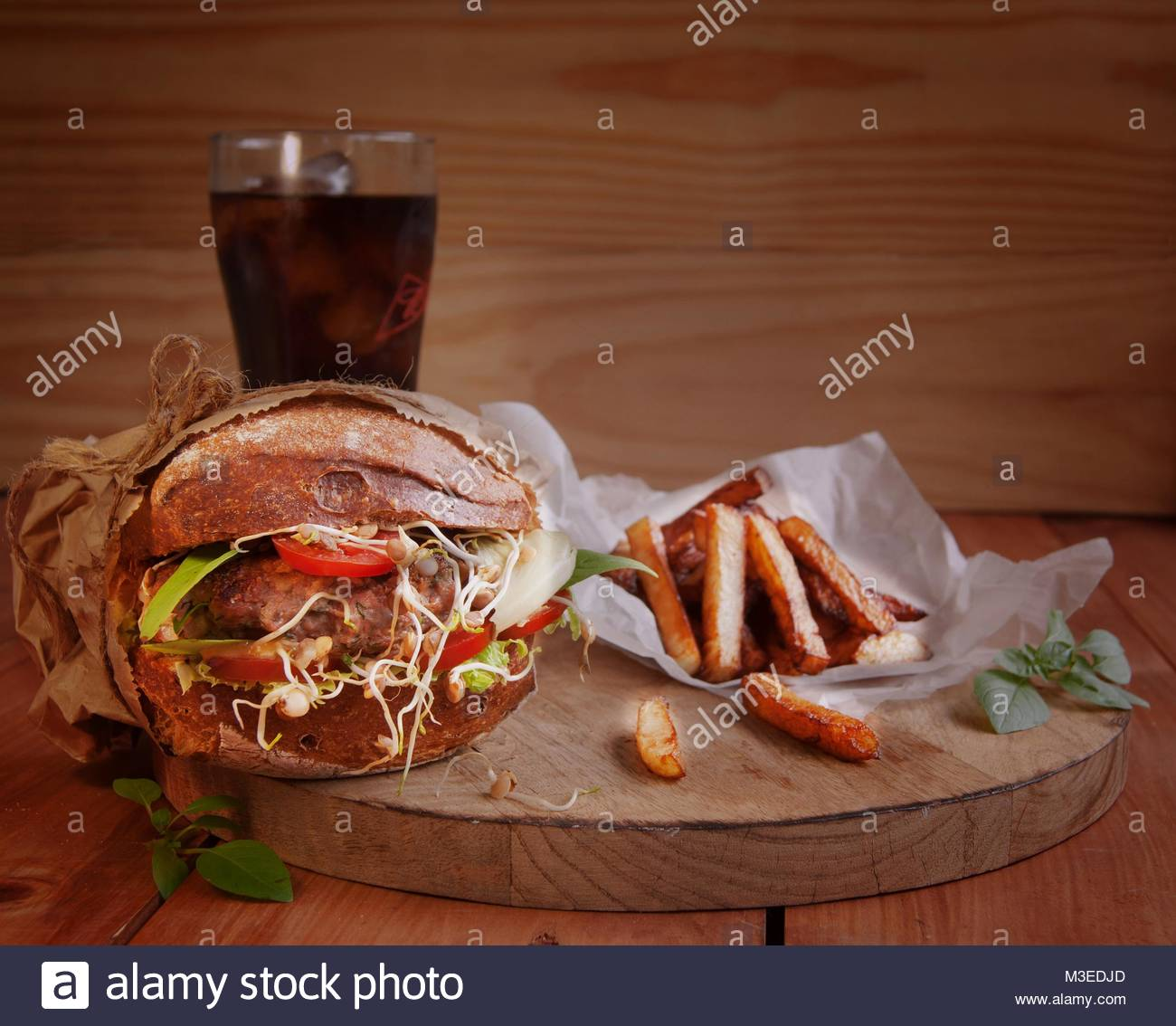Hamburger with fries and a drink on the wooden - Stock Image