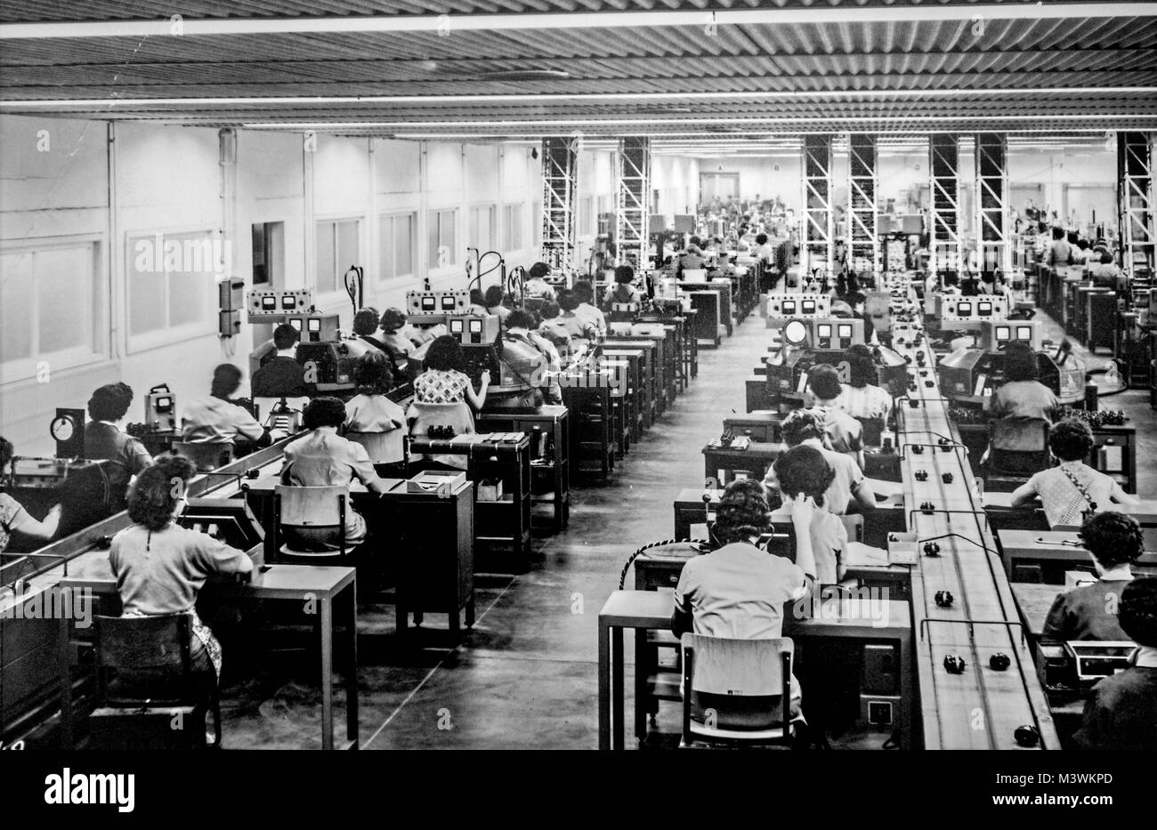 Old black and white archival photograph showing female workers manufacturing small electric motors in factory in - Stock Image