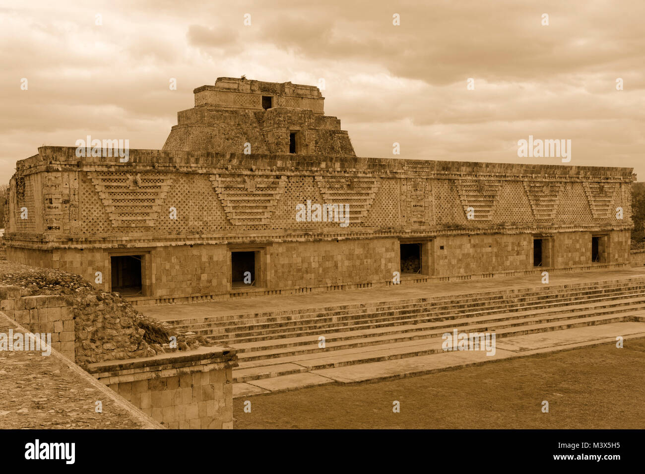 Sepia tone east building of the Nunnery Quadrangle with Pyramid of the Magician at the Mayan ruins of  Uxmal, Yucatan, - Stock Image