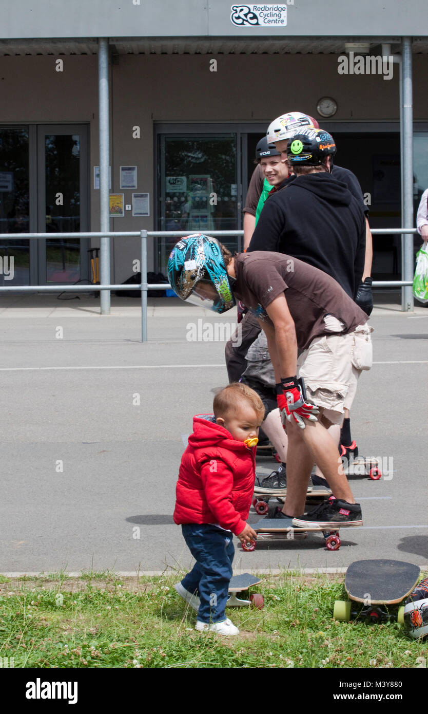 Baby with dummy walks in front of skateboarders warming up - Stock Image