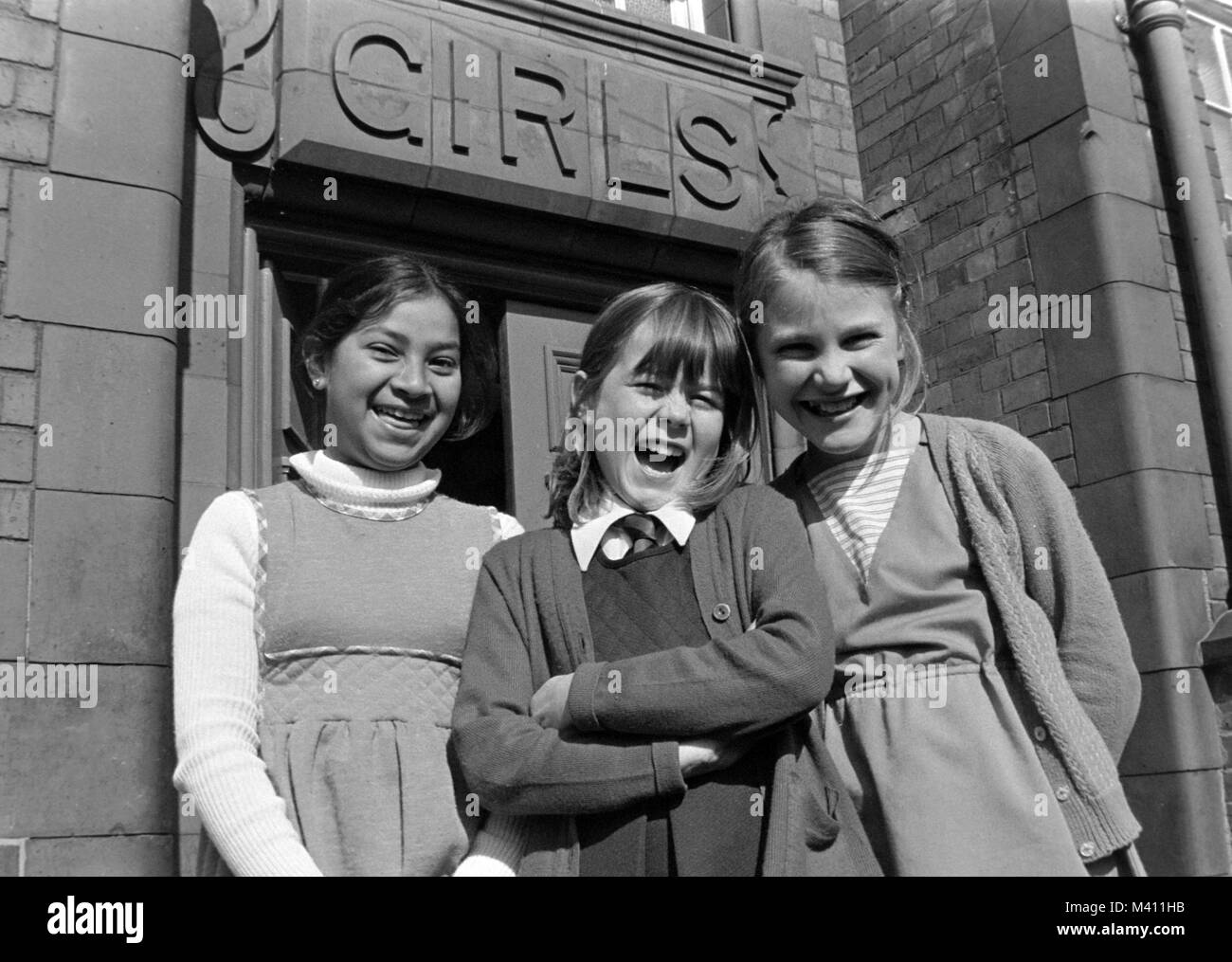 Three girls stood outside the Girls Entrance at Tiverton Junior and Infant School, Tiverton Road, Selly Oak, Birmingham, Stock Photo