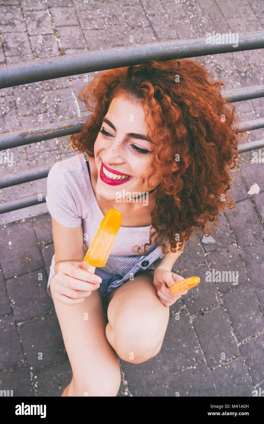 Redhead young woman eating ice creams in summer - Stock Image
