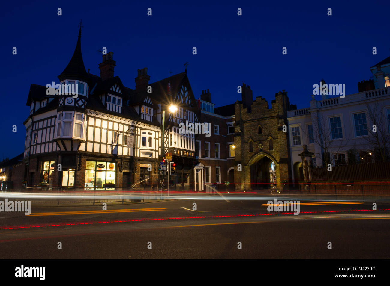 Light trails of vehicles at night in front of North Bar, a 15th century gate in the market town of Beverley in East - Stock Image