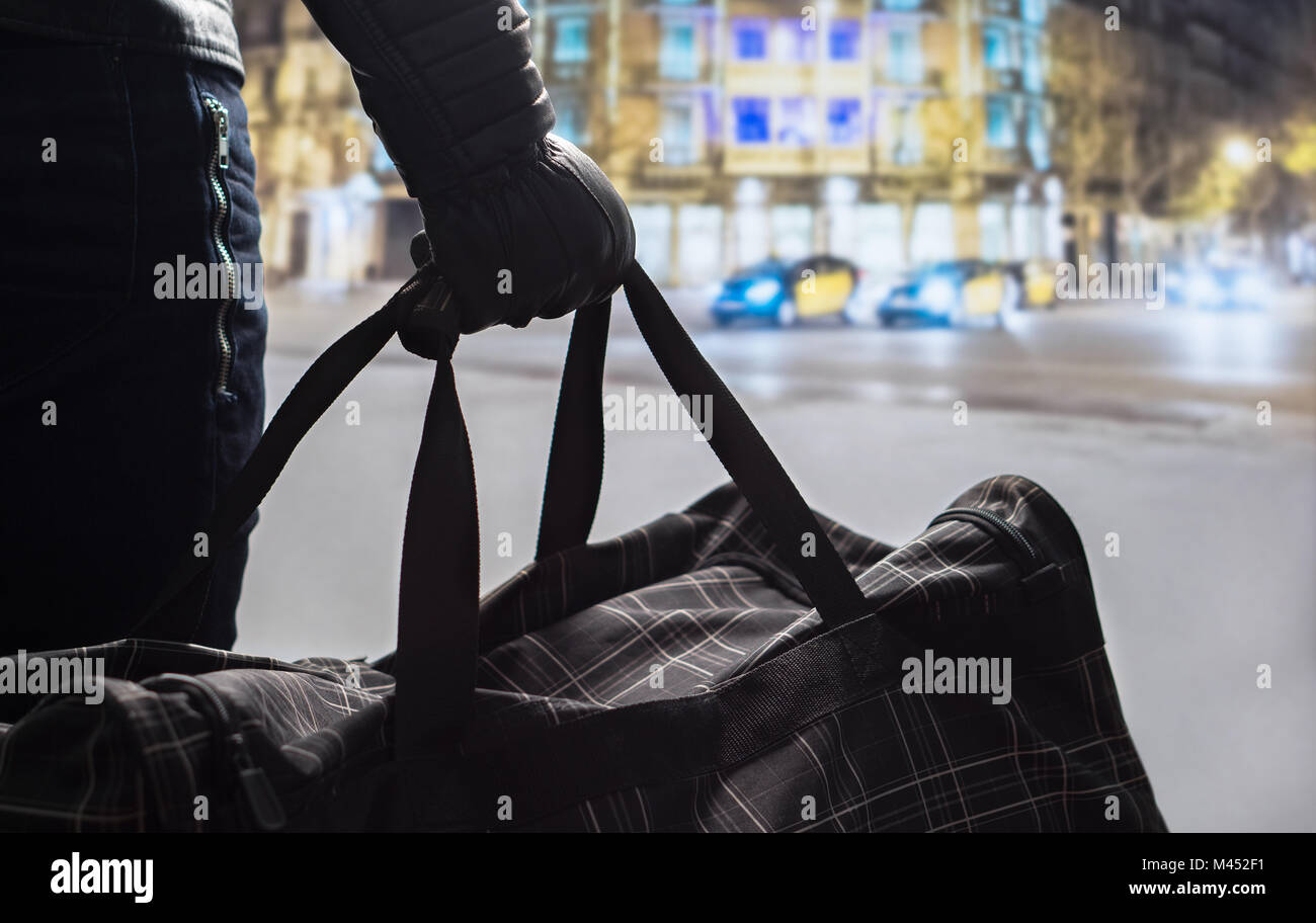 Terrorism and security threat concept. Terrorist at night. Suspicious man standing in city center holding black - Stock Image