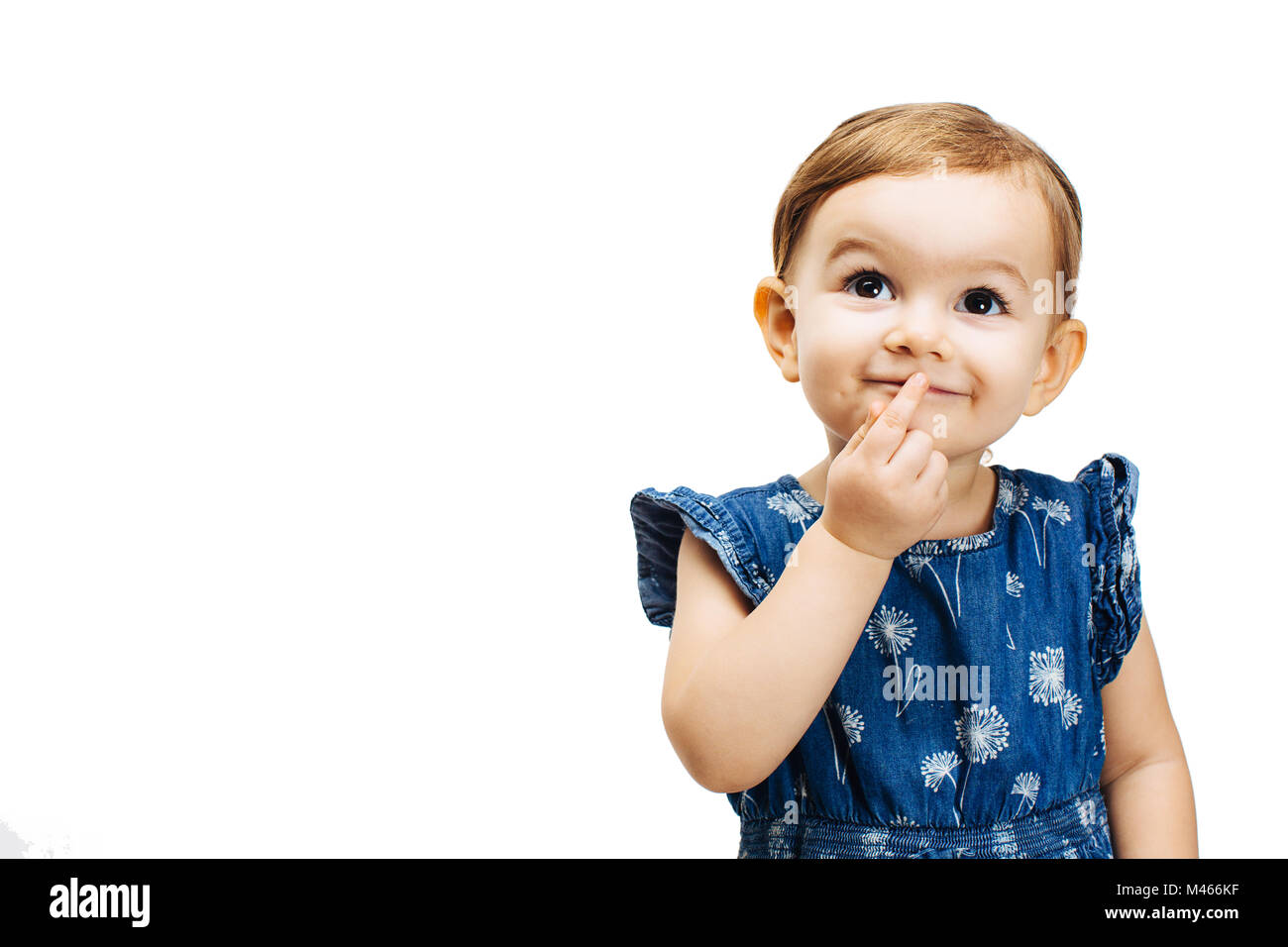 happy and curious toddler girl thinking with a finger by her mouth - Stock Image
