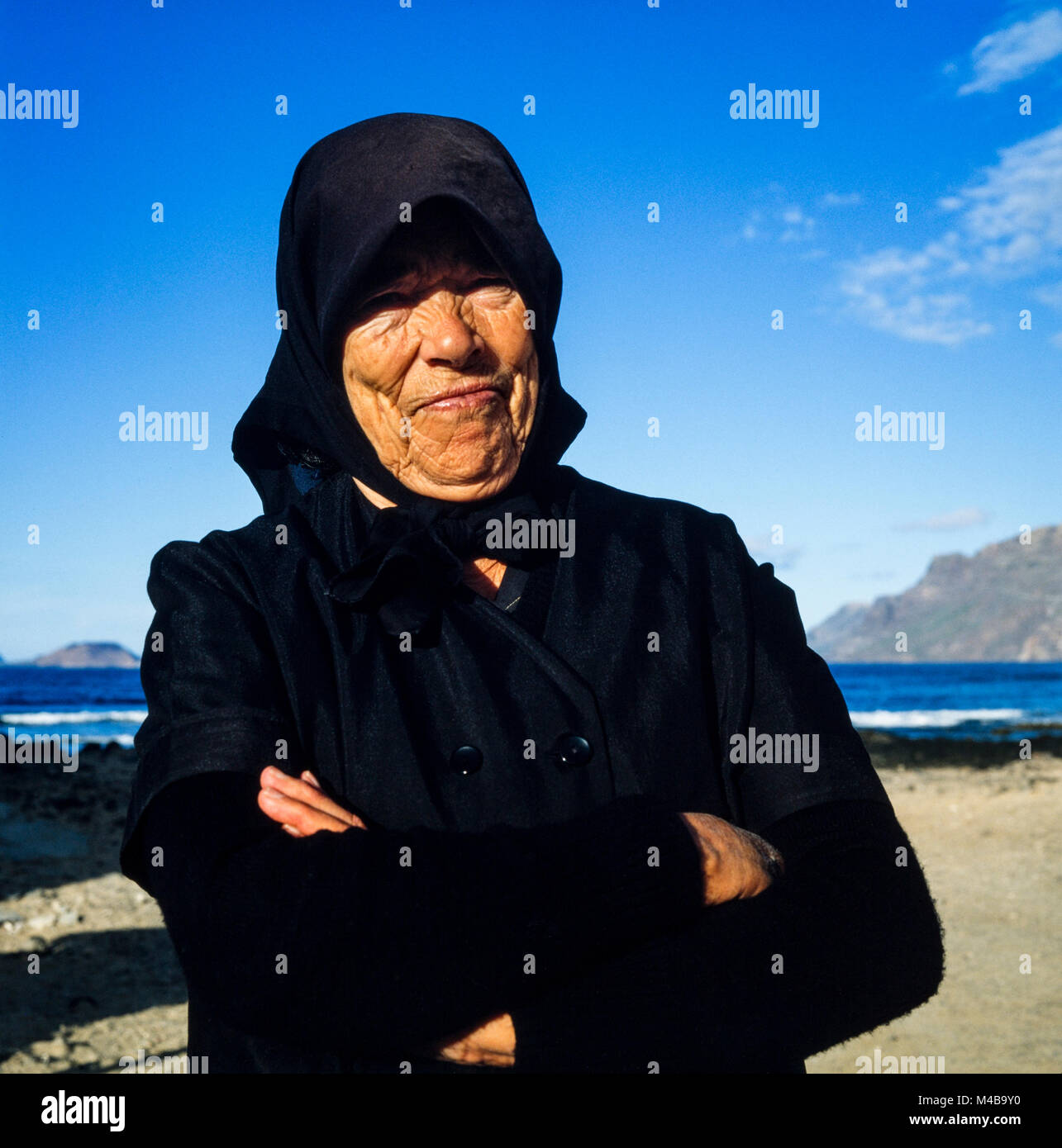 Old Canarian woman dressed in black wearing headscarf on a sunny day on a Lanzarote beach probably a widow, photographed Stock Photo