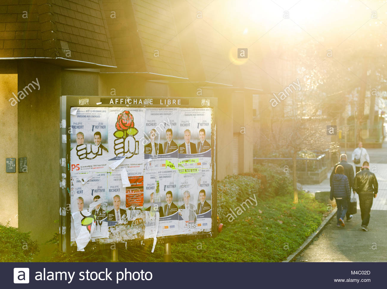Political advertising on French street with sun flare - Stock Image