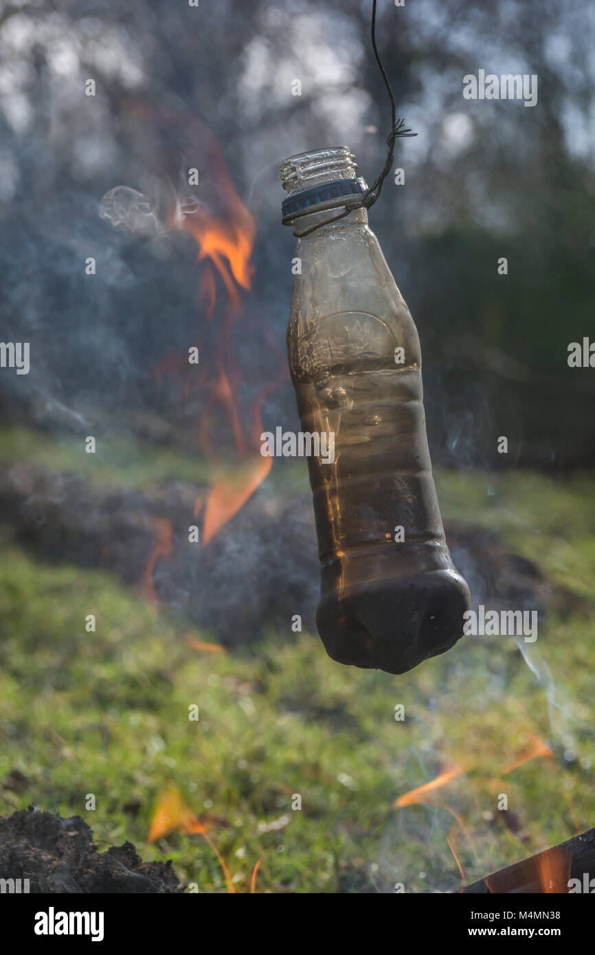 Survival skills / Überlebensfähigkeiten - boiling dirty / foul water in a plastic bottle to make it potable. - Stock Image