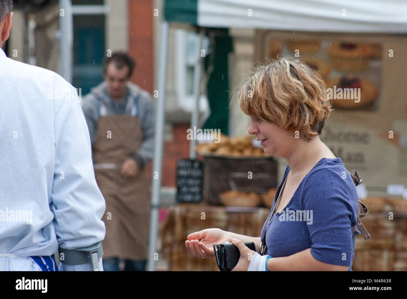 Young woman customer on a street market waits for her change - Stock Image