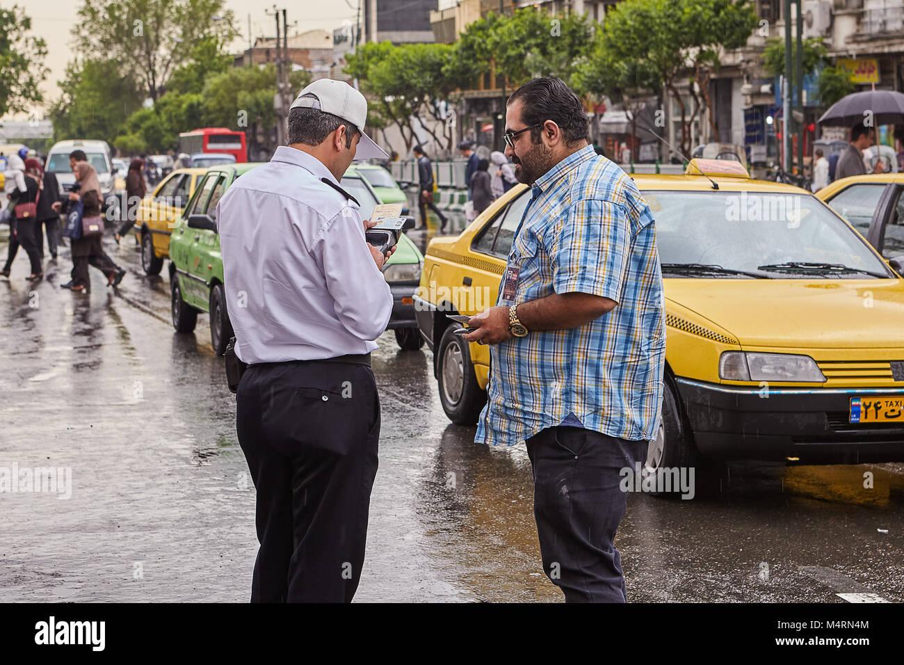 Tehran, Iran - April 29, 2017: Iranian policeman on the street checks driver's driver's license. - Stock Image