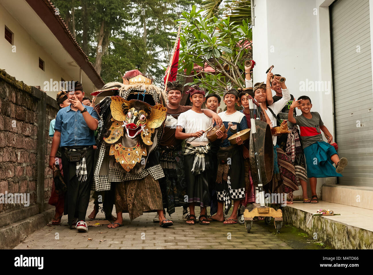 Local indonesian boys performing traditional lion dance with musical instruments on the street in Bali, Indonesia. Stock Photo