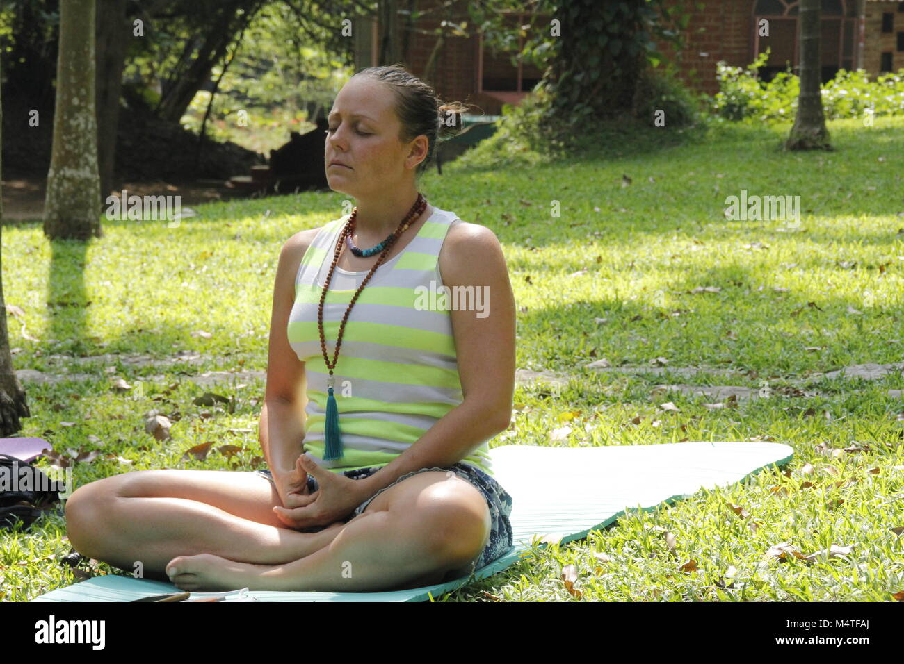 White woman meditating outdoors - Stock Image