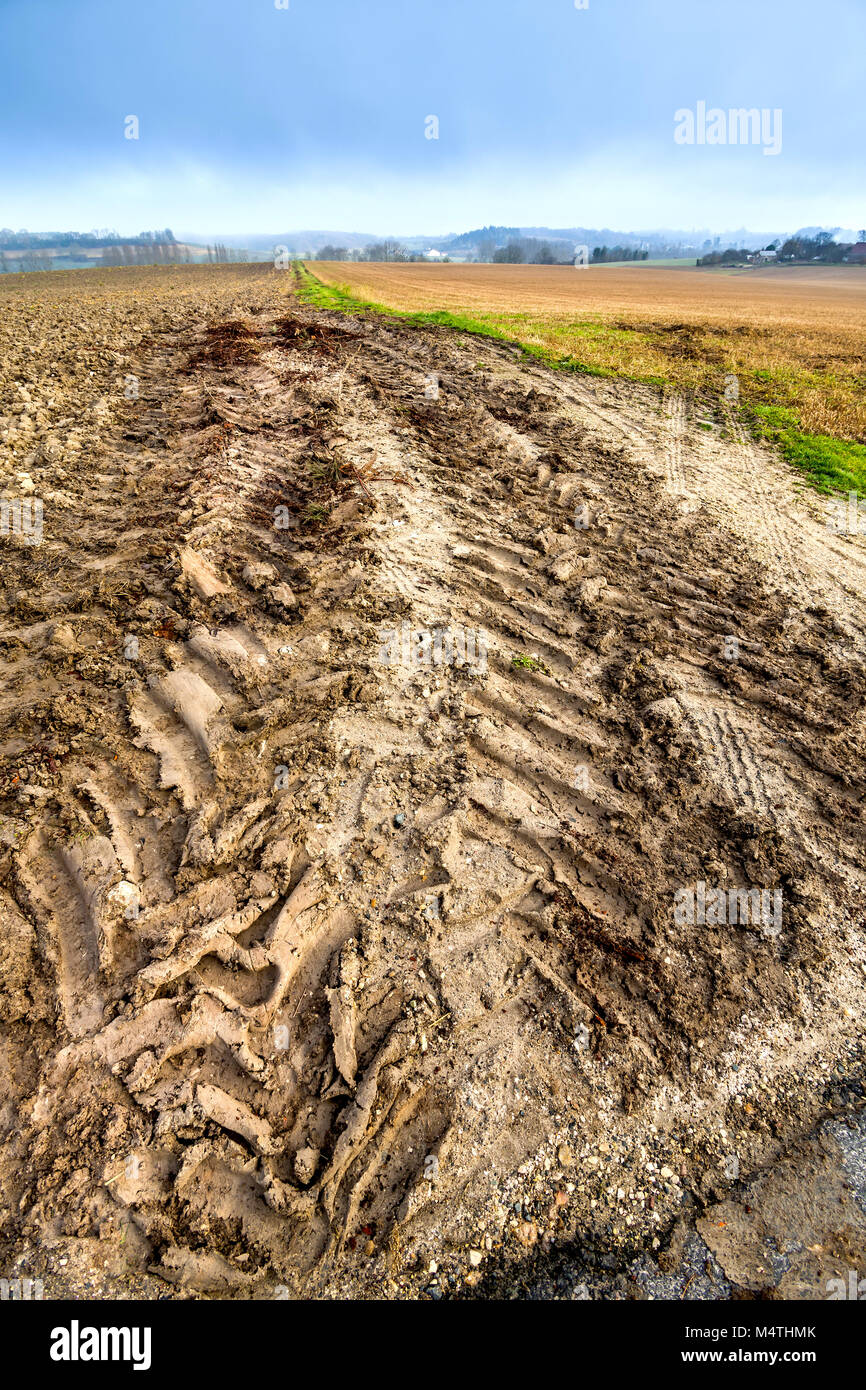 Muddy tyre tracks from field to road surface - France. - Stock Image