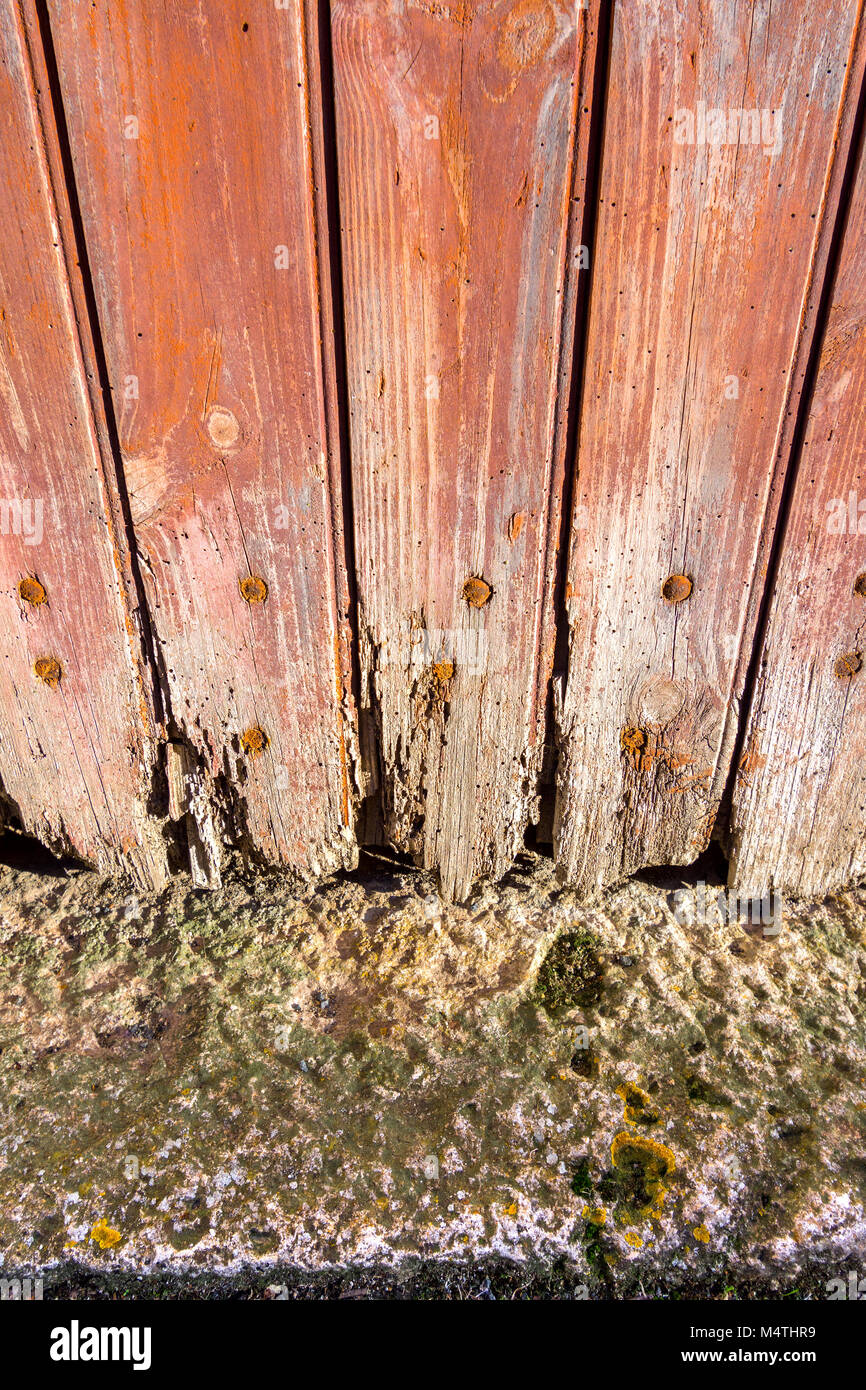 Rotten boards at foot of door. - Stock Image