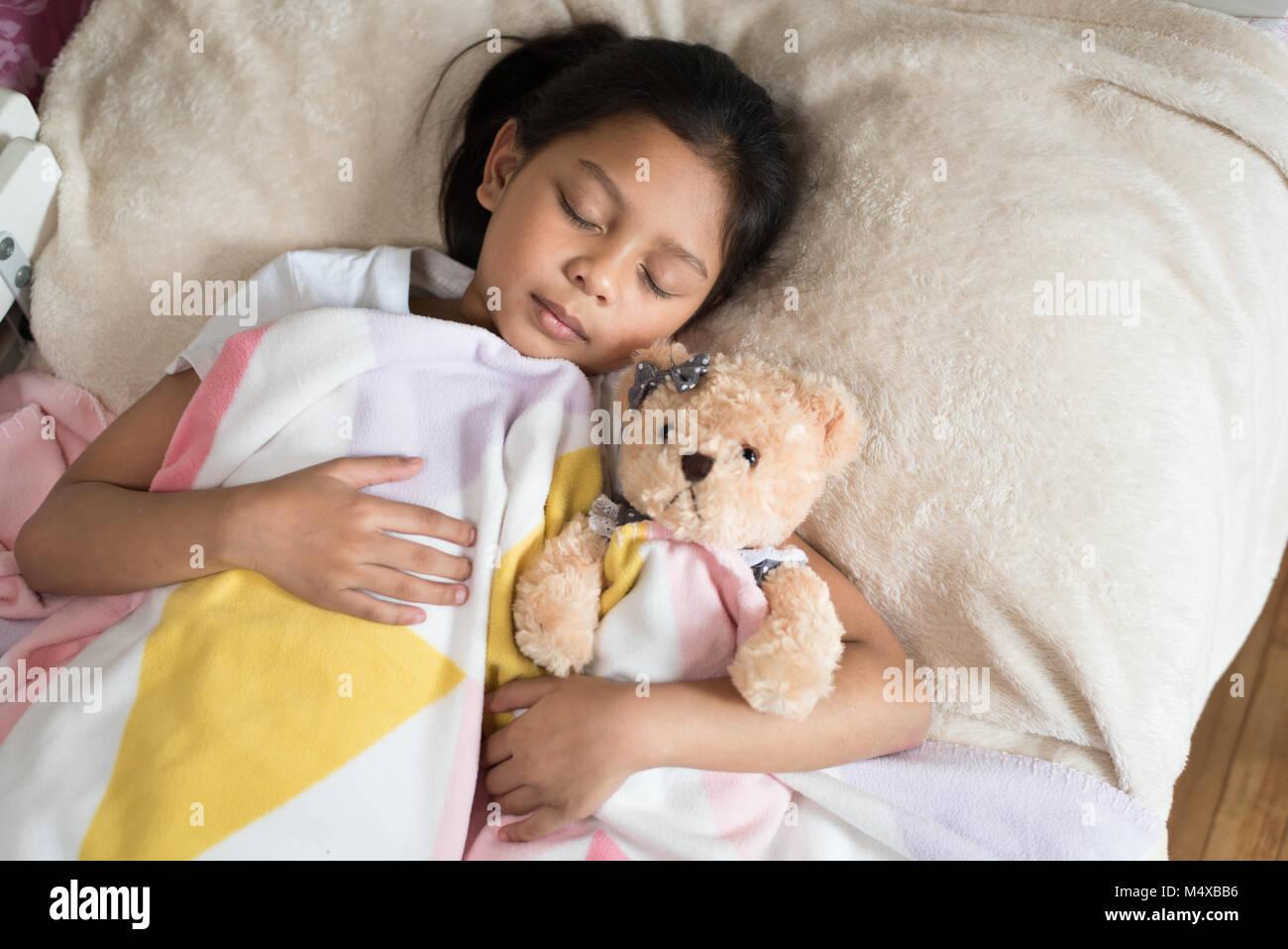 young little asian girl sleeping while hugging teddy bear. sleep concept
