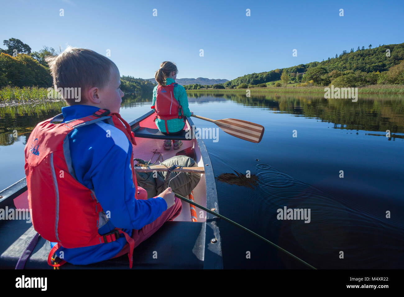 Family canoeing the Garavogue River to Lough Gill, Sligo town, County Sligo, Ireland. - Stock Image