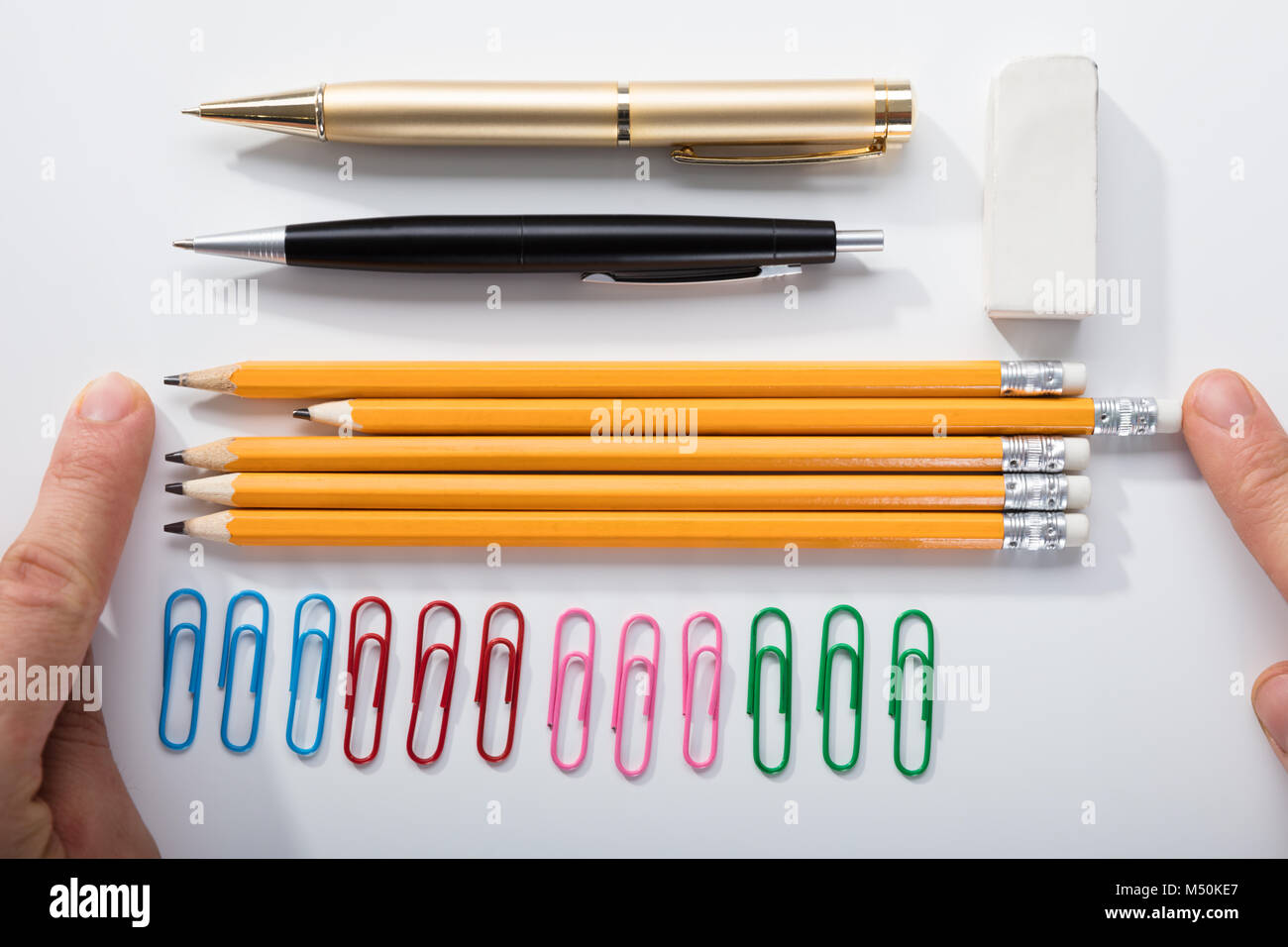 Person's Finger Arranging The Pencils With Row Of Pins Rubber And Pen On White Background Stock Photo