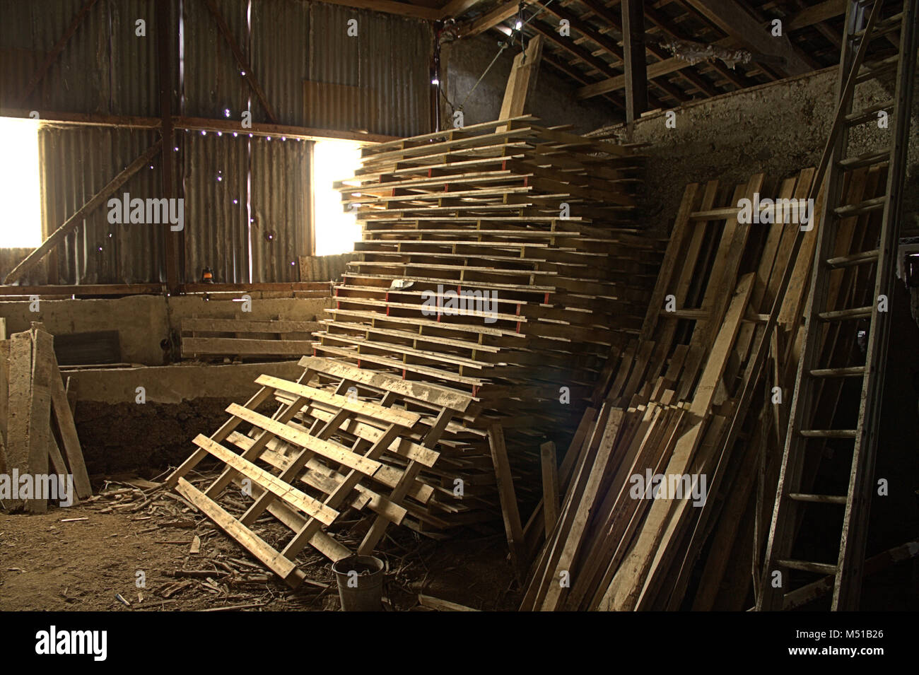 stack-of-pallets-in-a-barn-with-the-morning-sun-coming-through-the-M51B26.jpg