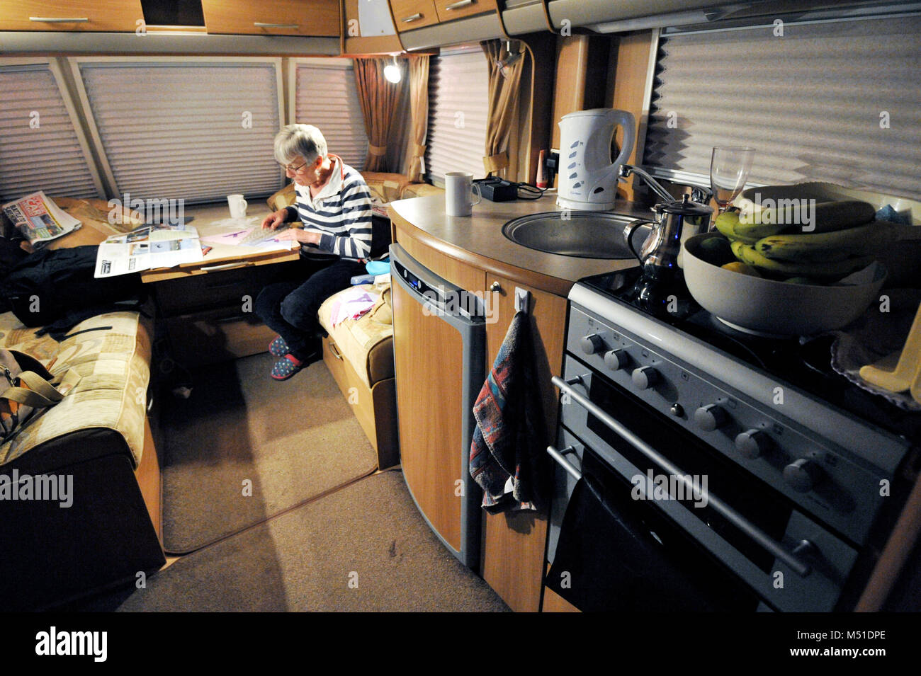 older woman seated in caravan at night - Stock Image