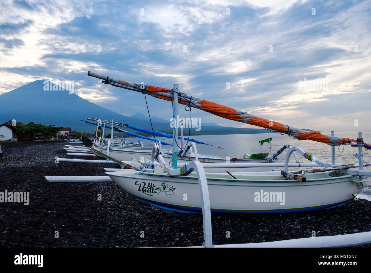 Traditional Balinese fishing boats or outrigger canoes ('jukung') on Amed Beach, with Agung volcano behind, - Stock Image