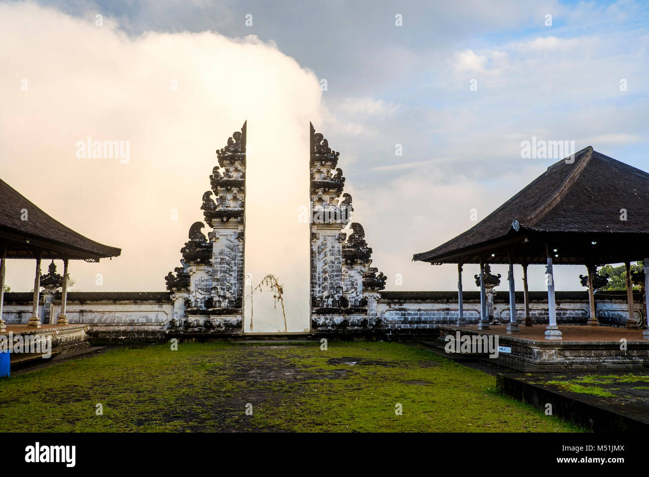 Clouds hinder the view through the split gateway ('candi bentar') of the outer sanctum, Pura Lempuyang temple, - Stock Image
