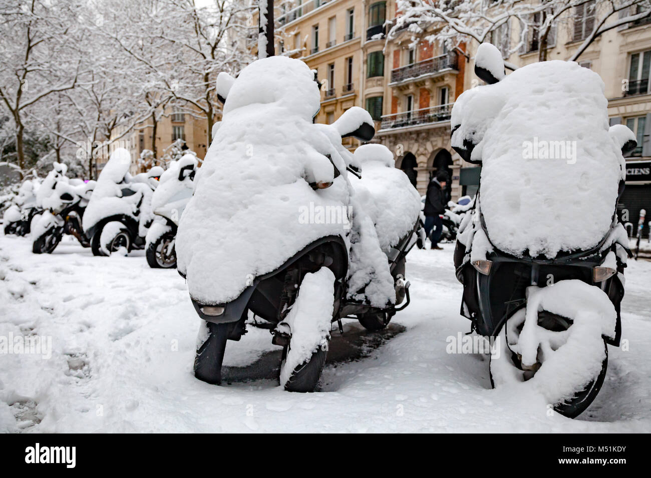 Snow covered motorcycles and scooters in Paris - Stock Image