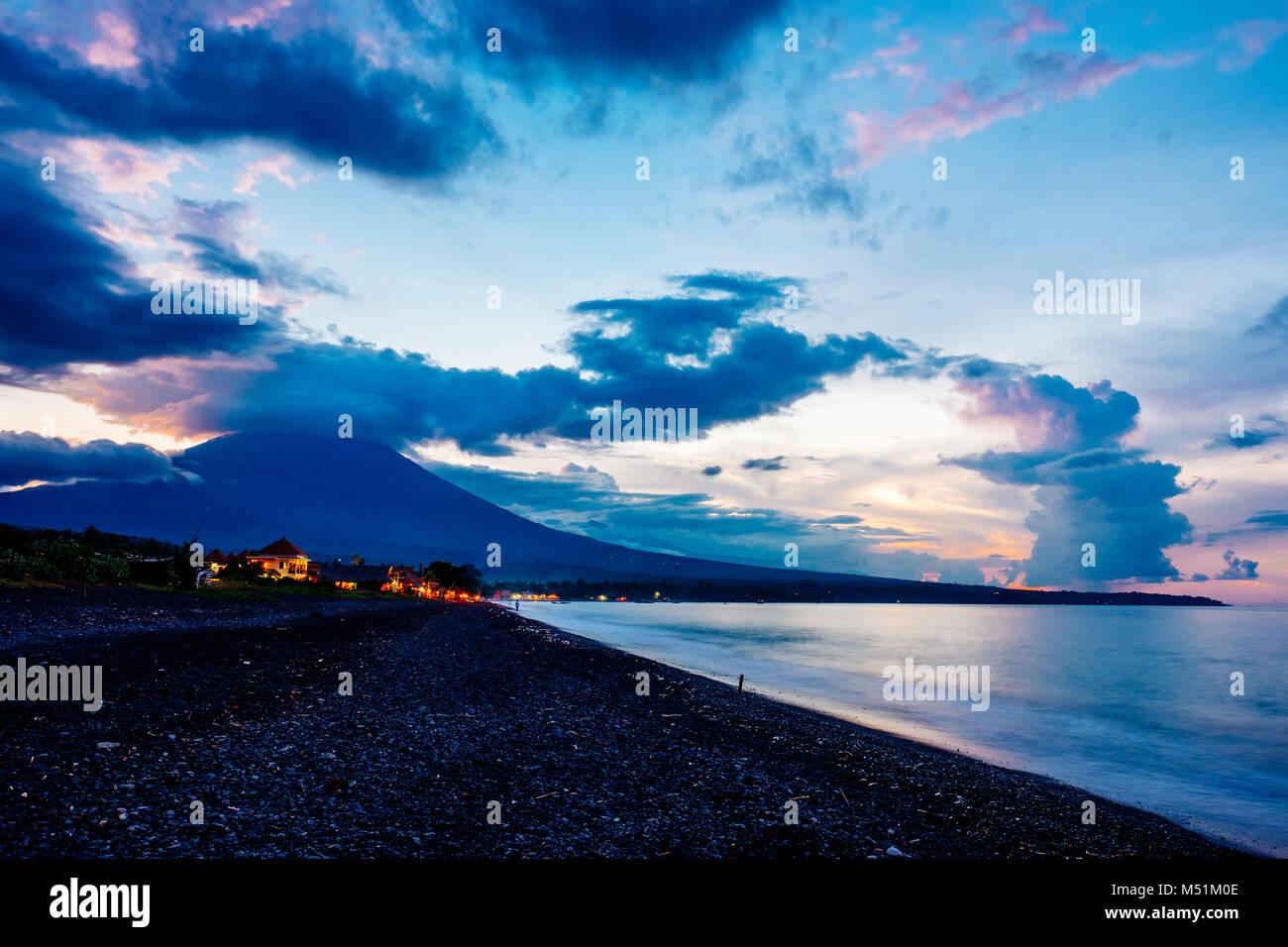 Mount Agung (Gunung Agung) seen from Amed Beach at dusk, Karangasem Regency, Bali, Indonesia. - Stock Image