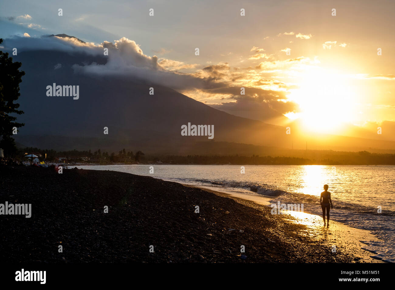 A woman walks on Amed beach with Gunung Agung volcano in the distance at sunset, Bali, Indonesia. - Stock Image