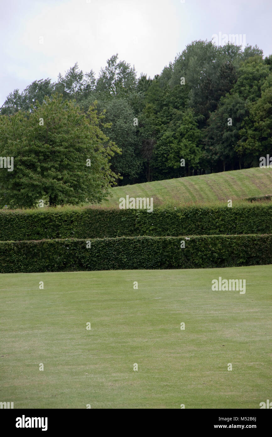 Patterns being made closely mown grass, trimmed hedges and trees - Stock Image