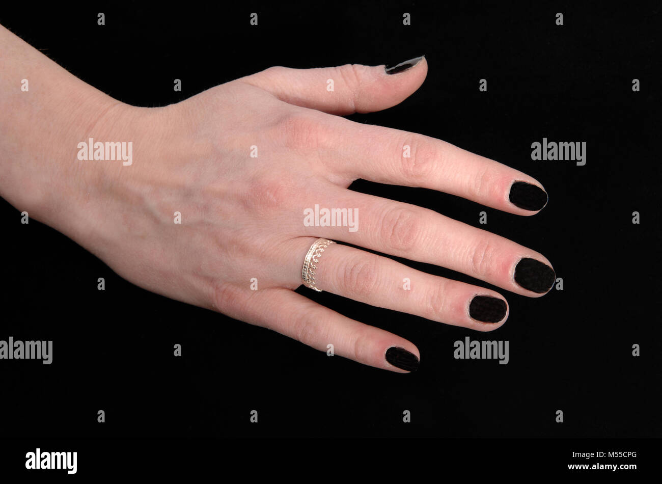 The hand of a woman on black background - Stock Image