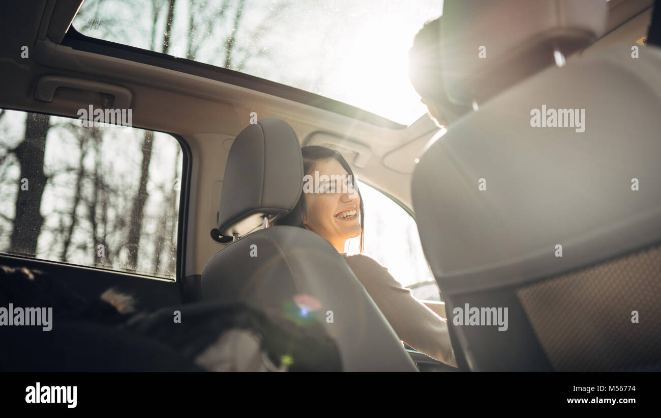 Young woman in a car,female driver looking at the passenger and smiling.Enjoying the ride,traveling,road trip concept.Driver - Stock Image
