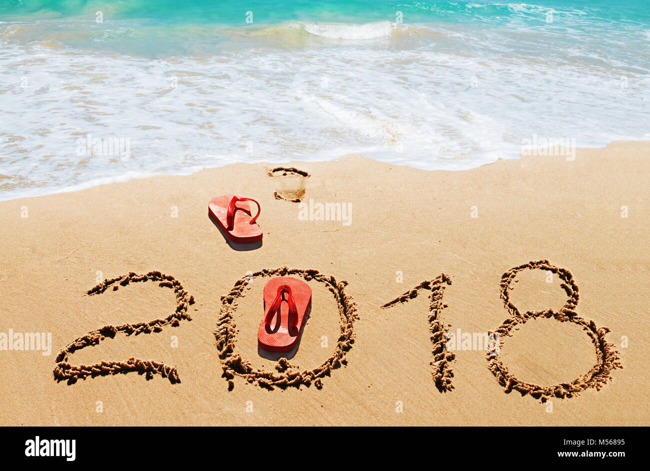 Red flip flops and digits 2018 on the beach - Stock Image
