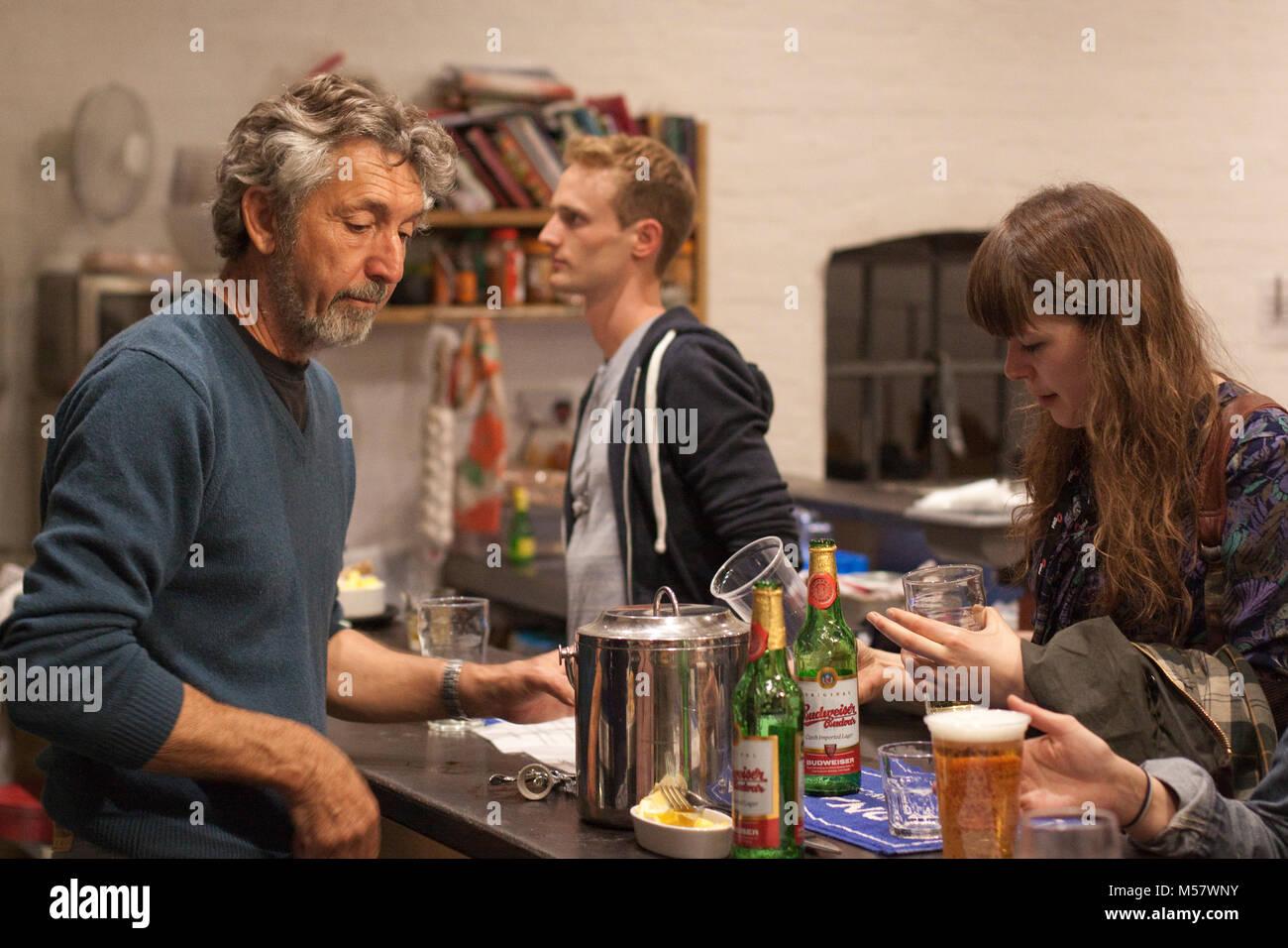 Bearded man serves at an arts centre bar - Stock Image