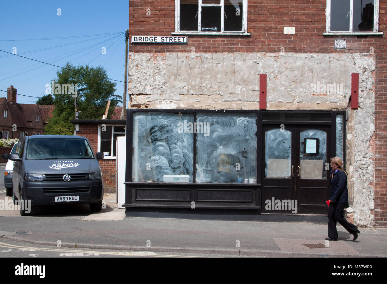 A woman walks past a shop having a makeover - Stock Image