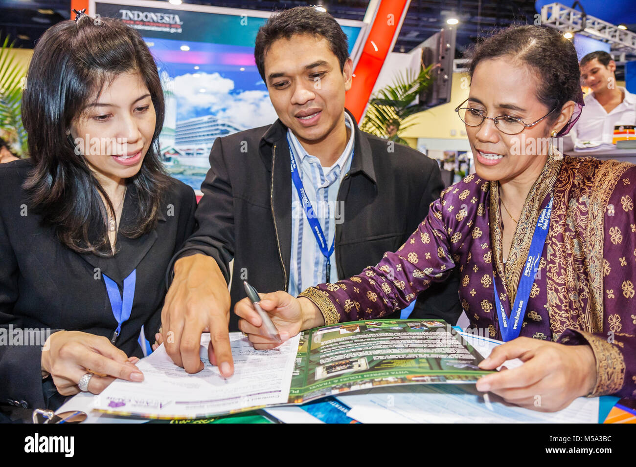 promotion suppliers Indonesian Asian woman women man co workers brochure read point - Stock Image