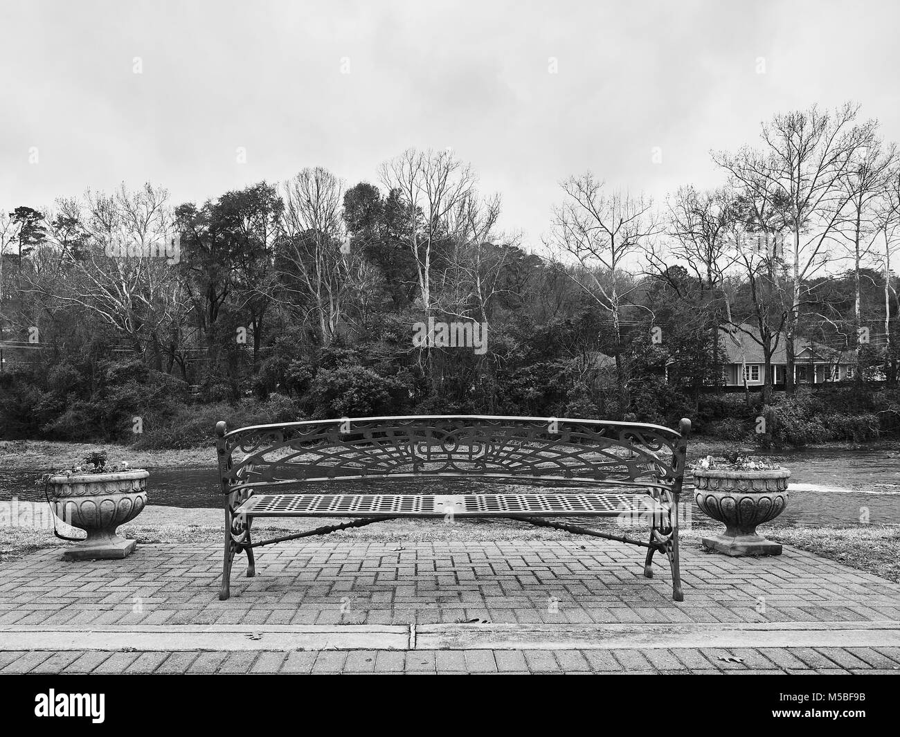 Unoccupied city park bench overlooking Autauga Creek with copy space, in Prattville Alabama, USA. - Stock Image