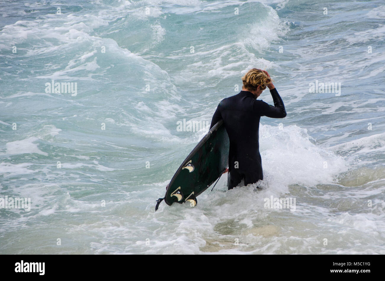 Male surfer walking through waves with surfboard. Freedom and expectation as male walks out to surf next wave. - Stock Image