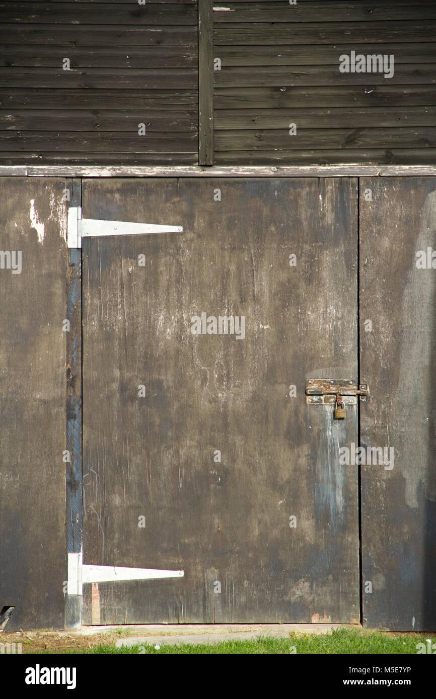 Enigmatic padlocked brown door - Stock Image