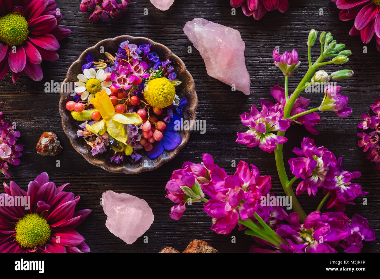 Spring Mix of Flowers, Rose Quartz and Garnet on Dark Table - Stock Image